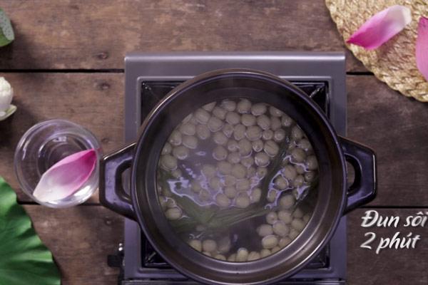 Lần lượt cho lá dứa, đường, hạt sen vào nấu